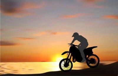 Fototapeta Mężczyzna na motocyklu w pobliżu morza na zachód słońca
