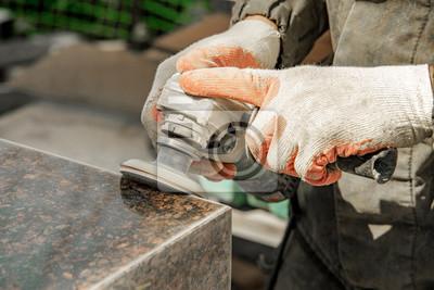 Fototapeta mężczyzna w ubraniu roboczym i rękawiczkach szlifuje kamień marmurowy szlifierką kątową. kamień szlifierski. produkcja zabytków. marmur