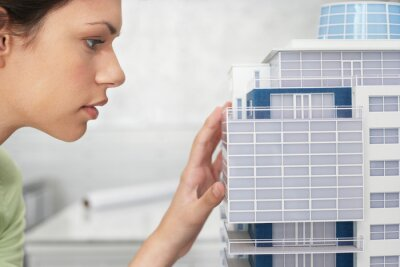 Fototapeta Mid adult woman inspecting architectural model profile close-up