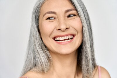 Fototapeta Middle aged happy mature asian woman, senior 50 year lady looking away, isolated on white closeup headshot. Ads of antiaging uv protection whitening menopause dry skincare, plastic surgery.