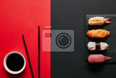 Fototapeta mieszkanie leżał z sosem sojowym w misce, pałeczkach i sushi nigiri zestaw na czarnej płytce łupków na czerwonym i czarnym tle
