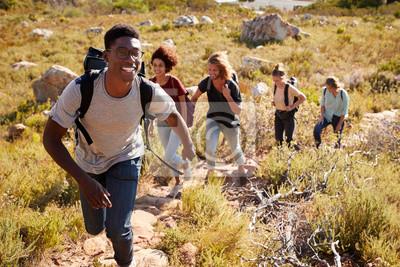 Fototapeta Millennial African American man leading friends hiking single file uphill on a path in countryside