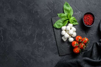 Fototapeta Mini mozzarella cheese, Basil leaves and cherry tomatoes, cooking Caprese salad. black background. top view. Copy space.