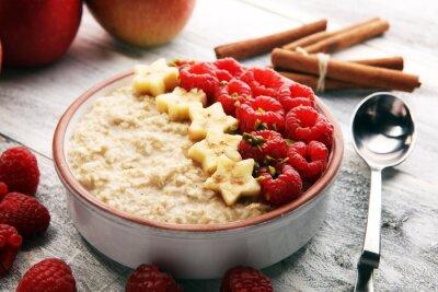 Miska owsianki owsianej z bananem, malinami, kokosem i sosem karmelowym na rustykalnym stole, gorące i zdrowe jedzenie na śniadanie