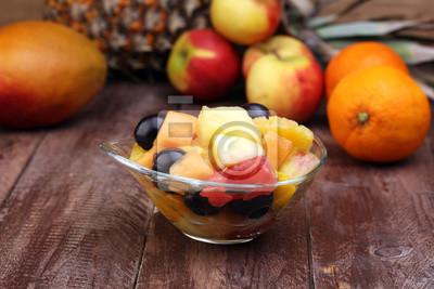 Miska zdrowe sałatki ze świeżych owoców na tle drewnianych.