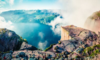 Fototapeta Misty morning view of popular Norwegian attraction Preikestolen. Great summer scene of the Lysefjorden fjord, located in the Ryfylke area in southwestern Norway. Beauty of nature concept background.