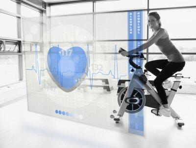 Fototapeta Młoda atrakcyjna dziewczyna robi rower treningowy z futurystycznym Interf