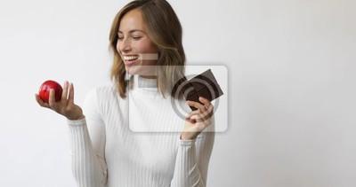 Młoda brunetki kobieta na białym tle ono uśmiecha się i śmia się kamera podczas gdy trzymający czekoladę i owocowego rozważanie