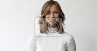 Młoda brunetki kobieta na białym tle uśmiecha się i śmia się do kamery i dotyka włosów