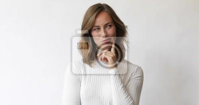 Młoda brunetki kobieta rozważa i ono uśmiecha się kamera na białym tle