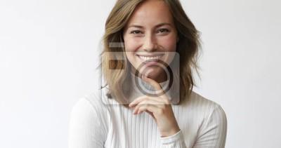 Młoda brunetki kobieta rozważa i ono uśmiecha się kamery zbliżenie na białym tle