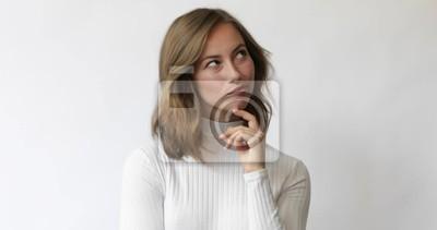 Młoda brunetki kobieta rozważa i ono uśmiecha się na białym tle podczas gdy patrzejący wokoło