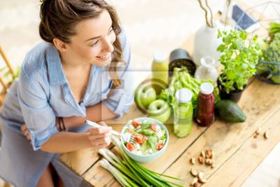 Fototapeta Młoda i szczęśliwa kobieta jedzenia zdrowej sałatki siedzącej na stole z zielonych świeżych składników kryty