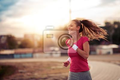 Fototapeta Młoda kobieta działa na ulicy miasta