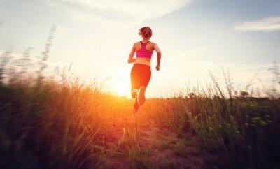 Fototapeta Młoda kobieta działa na wiejskiej drodze na zachód słońca