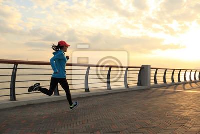 Fototapeta Młoda kobieta fitness biegacz na wschód słońca nad morzem