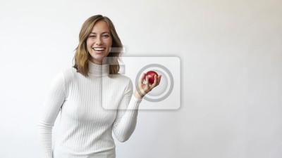 młoda kobieta na białym tle rzuca czerwone jabłko w powietrze z uśmiechem i śmieje się slowmotion