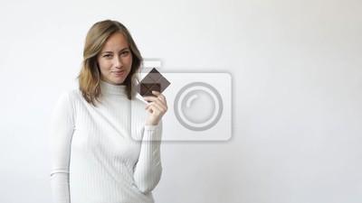 młoda kobieta na białym tle z czekoladą uśmiecha się śmiech kuszony i rozważający slowmotion