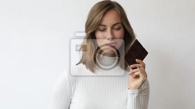 młoda kobieta na białym tle z czekoladą uśmiecha się śmieje i biorąc pod uwagę zbliżenie slowmotion