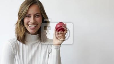 młoda kobieta na białym tle z czerwonym jabłkiem przed okiem uśmiechnięty i śmieje się zbliżenie slowmotion