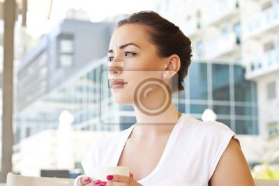 Młoda kobieta picia herbaty w kawiarni na zewnątrz pomieszczeń