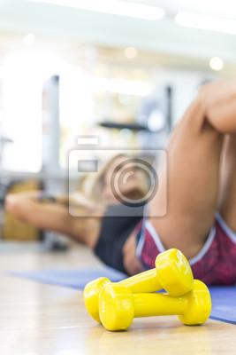 Młoda kobieta robi abs ćwiczenia na siłowni.