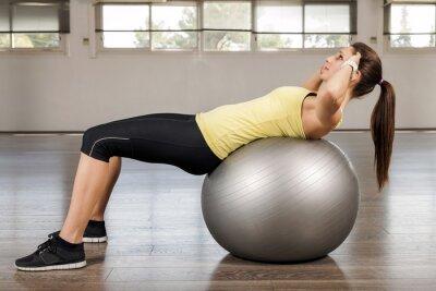 Fototapeta Młoda kobieta robi brzucha na piłce do ćwiczeń
