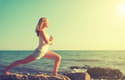 Fototapeta Młoda kobieta robi joga na plaży