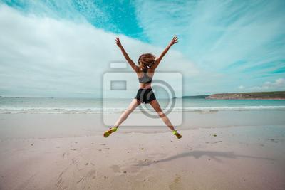 Fototapeta Młoda kobieta robi star skoki na plaży