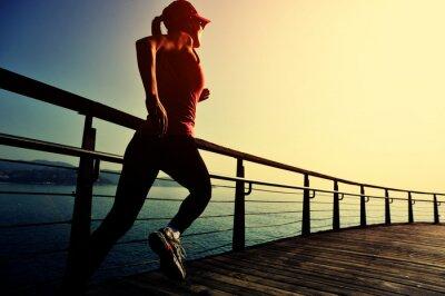 Fototapeta młoda kobieta siłownia działa na nadmorskiej promenadzie sunrise