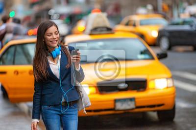 Fototapeta Młoda kobieta spaceru w Nowym Jorku za pomocą aplikacji telefonu na przejażdżkę taksówką ze słuchawkami dojazdy z pracy. Azjatyckiej dziewczyny szczęśliwy texting na smartphone. Miejski spacer dojeżdż