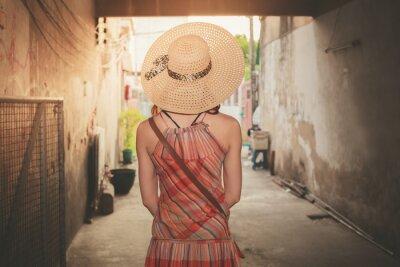 Fototapeta Młoda kobieta w alejce na zachodzie słońca