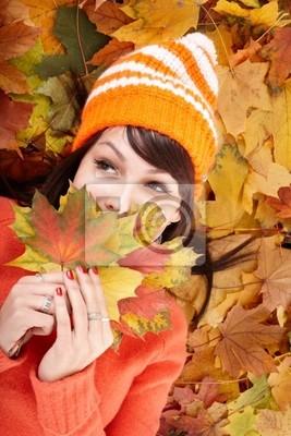 Młoda kobieta w jesiennej pomarańczowy opuszcza.