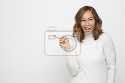 młoda kobieta, wskazując na copyspace wygląda w aparacie