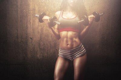 Fototapeta Młoda kobieta wykonywania ćwiczeń ćwiczenia z jej silnego ciała mięśni