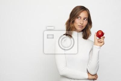młoda kobieta z czerwoną brzoskwinią wygląda na lewo