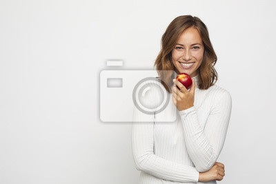 młoda kobieta z czerwoną brzoskwinią wygląda w aparacie
