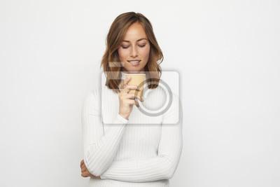 młoda kobieta z filiżanką kawy patrzy w dół gryzie wargę