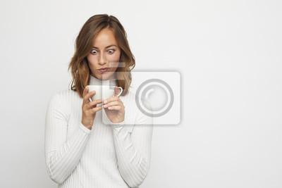 młoda kobieta z filiżanką kawy wygląda śmiesznie