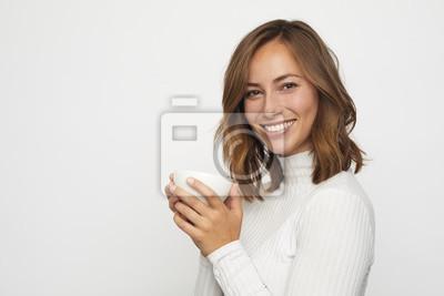 młoda kobieta z filiżanką kawy wygląda w aparacie