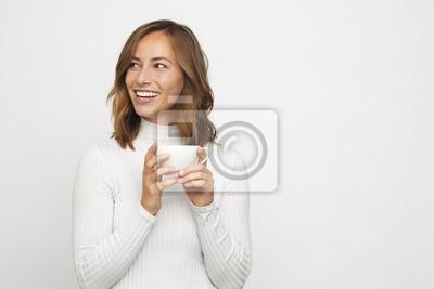 Fototapeta młoda kobieta z filiżanką kawy wygląda w lewo