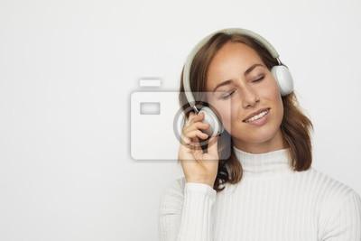 młoda kobieta z zamkniętymi oczami słuchawek