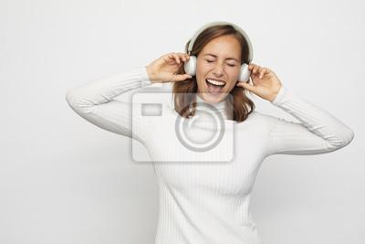 młoda kobieta ze słuchawkami śpiewa oczy zamknięte