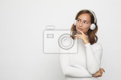 młoda kobieta ze słuchawkami wygląda na lewo