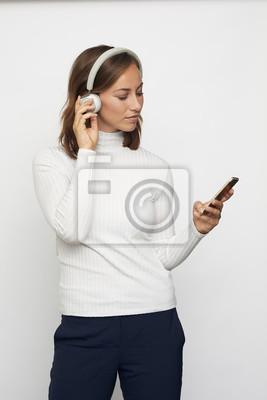 Fototapeta młoda kobieta ze słuchawkami wygląda na telefon