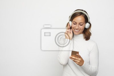 młoda kobieta ze słuchawkami wygląda na telefon patrzy w dół