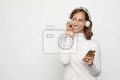 młoda kobieta ze słuchawkami wygląda na telefon wygląda w lewo