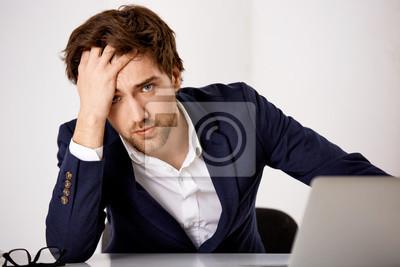 Młoda mylić biznesmen siedzi na biurku