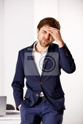 Młoda mylić biznesmen stojący przy biurku i Hol