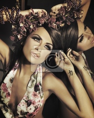 Młoda piękna brunetka stwarzających w lustrze